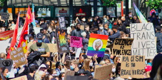 hundreds of protesters marching with rainbow flags and signs