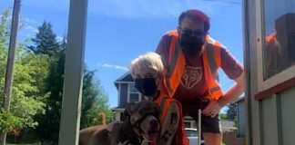 A couple and their dog pose with a bucket full of trash they collected through AdoptOneBlock